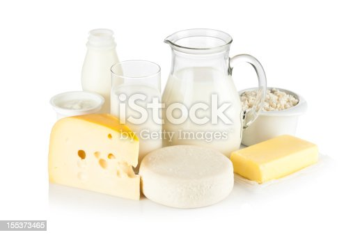Image of dairy products shot on reflective white backdrop. Includes: milk, various types of cheese, butter, ricotta, milk cream and yogurt. A milk pitcher and a glass of milk are in the center while the rest of the products are around them. A soft shadow is visible in the foreground. The predominant color is white. DSRL studio shot with Canon EOS 5D Mk II