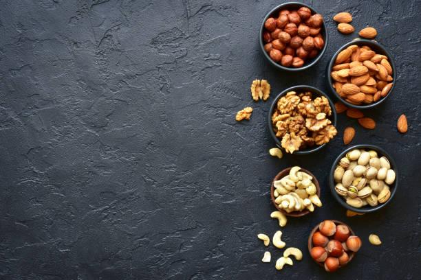 assortment of nuts on  a black slate or stone background - frutos secos imagens e fotografias de stock