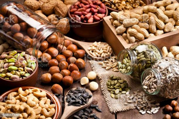 Horizontal shot of a rustic wood table filled with a large assortment of nuts like pistachios, hazelnut, pine nut, almonds, pumpkin seeds, sunflower seeds, peanuts, cashew and walnuts. Some nuts are in brown bowls and others in glass jars. Predominant color is brown. DSRL studio photo taken with Canon EOS 5D Mk II and Canon EF 100mm f/2.8L Macro IS USM