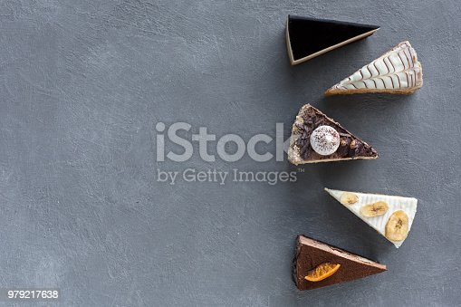 Assortment of pieces of cake on grey table, copy space. Several slices of delicious desserts, restaurant menu concept