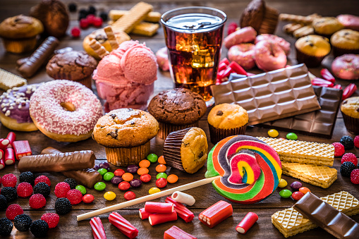 Assortment of products with high sugar level like candies, gummy candies, soda, donuts, chocolate, lollipop, wafers and cupcakes on rustic wooden table. Low key DSLR photo taken with Canon EOS 6D Mark II and Canon EF 24-105 mm f/4L