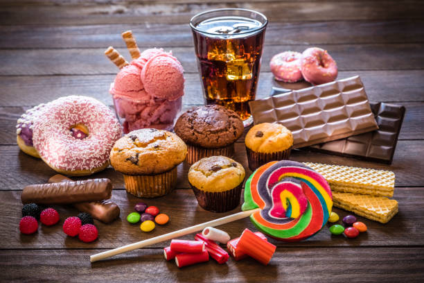 Assortment of products with high sugar level Assortment of products with high sugar level like candies, gummy candies, donuts, soda, chocolate, lollipop, wafers and cupcakes on rustic wooden table. Low key DSLR photo taken with Canon EOS 6D Mark II and Canon EF 24-105 mm f/4L unhealthy eating stock pictures, royalty-free photos & images