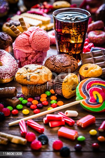 Assortment of products with high sugar level like candies, gummy candies, donuts, soda, chocolate, lollipop, wafers and cupcakes on rustic wooden table. Low key DSLR photo taken with Canon EOS 6D Mark II and Canon EF 24-105 mm f/4L