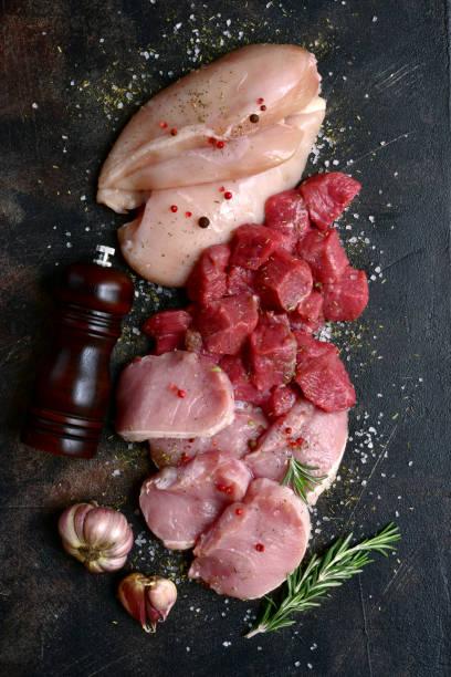 Sortiment von rohem frischem weiß und rotem Fleisch: Hähnchenbrust, Rind- und Schweinefilet mit Gewürzen – Foto