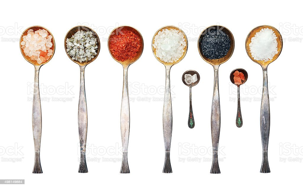 Assortment of salt in a metal spoon stock photo