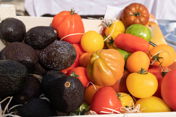 assortment of several varieties of tomatoes and avocados on a market stall stock photo