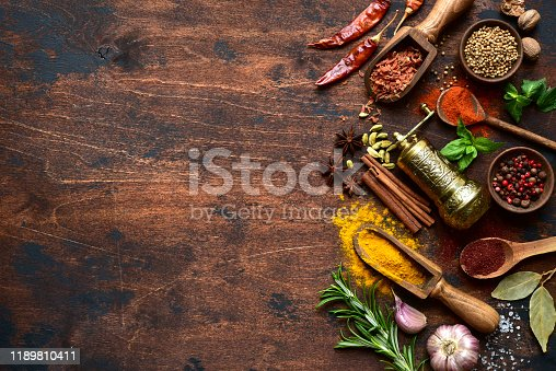 Assortment of spices and herbs on a dark rustic wooden background. Top view with copy space.