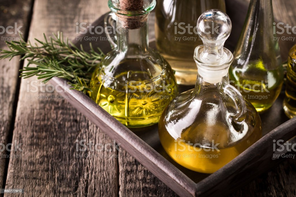 Assortment of spicy sunflower,corn,sesame seeds ,avocado ,grape seeds oils with herbs and spices in different bottles on wooden background stock photo