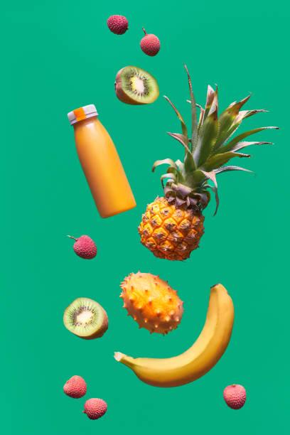 Assortment of tropical fruits and orange smoothie bottle on green background. Pineapple, kiwano, kiwi , lichee and banana - exotic fruits, levitation and vitamin balance. stock photo