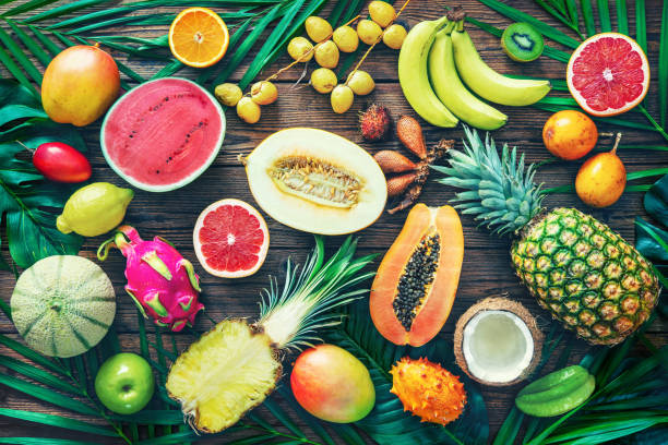 Assortment of tropical fruits with leaves of palm trees and exotic plants on dark wooden background stock photo