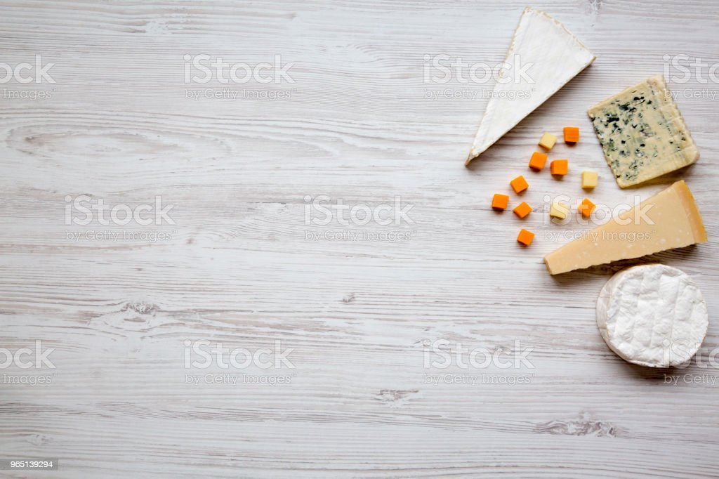 Assortment of various cheese on a white wooden background. Space for text. From above, flat lay. royalty-free stock photo