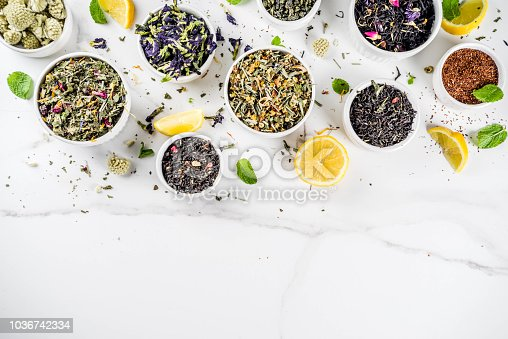 Assortment of various dry tea - classic black and green, flower, fruit, berry and herbal tea blends, with lemon and mint, White marble background copy space top view