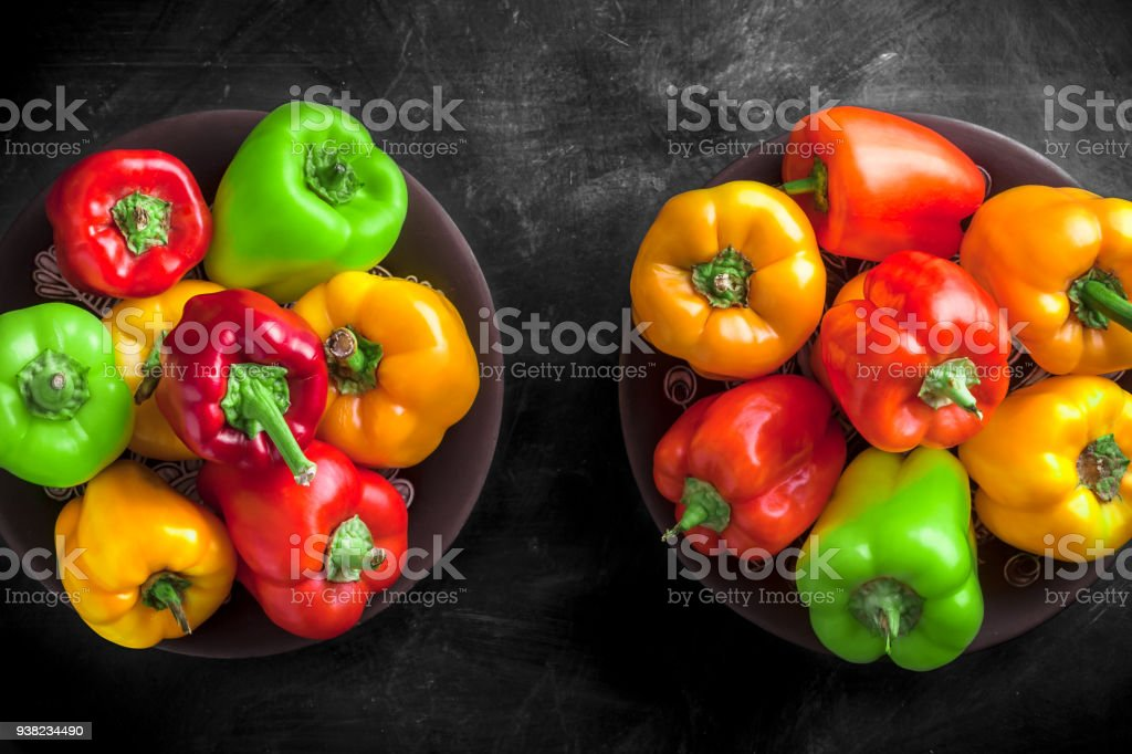 Assortment overhead arrangement of bell peppers in two black plates stock photo