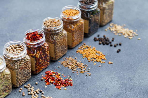 Assortments of spices, white pepper, chili flakes, lemongrass, coriander and cumin seeds in jars on grey stone background. Copy space. stock photo