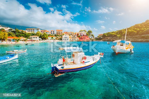 Assos village on Kefalonia island, Greece. White boats in the emerald rippled sea water bay.