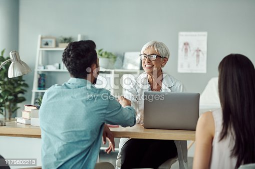 Cropped shot of a confident mature female doctor meeting with a young couple in her office at the hospital