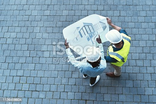 High angle shot of two engineers looking at a blueprint