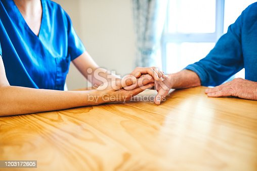 Cropped shot of an unrecognizable female nurse consoling a senior man in a nursing home