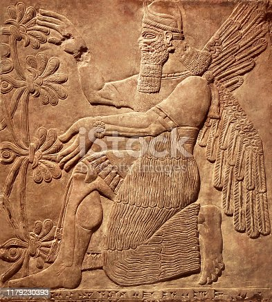 Assyrian wall relief of a winged genius. Old carving panel from the Middle East history. Remains of the culture of ancient Babylonian and Sumerian civilization. Amazing art of Mesopotamia.