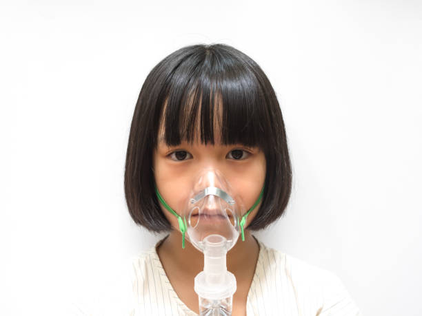 Asthma breathing in children problem concept. Asia pediatric patient kid girl with inhaler sick with bronchitis isolated on white background with copyspace. Asthma breathing in children problem concept. Asia pediatric patient kid girl with inhaler sick with bronchitis isolated on white background with copyspace. oxygen mask stock pictures, royalty-free photos & images