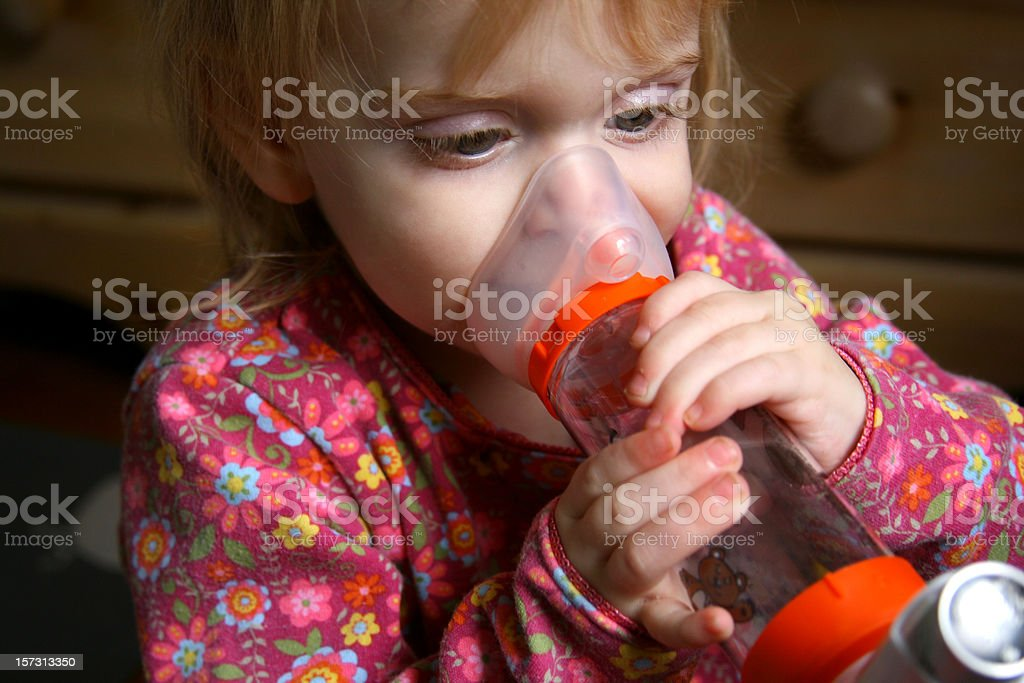 Asthma Girl: Toddler Holds Inhaler After Attack stock photo