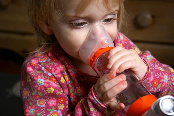 Asthma Girl: Toddler Holds Inhaler After Attack stock photo