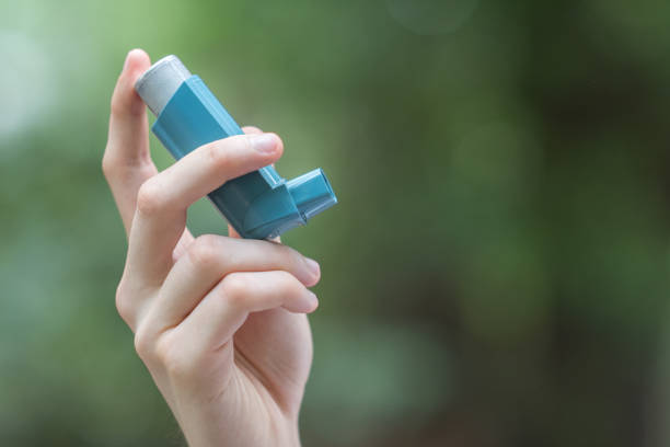 Asthma medecine inhaler holded by a man stock photo