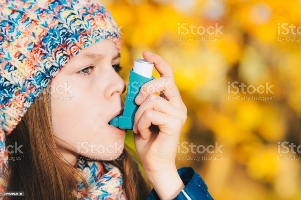 Asthma patient girl inhaling medication for treating shortness of breath and wheezing in a park stock photo
