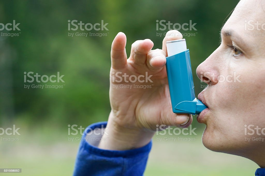 Asthma patient inhaling medication stock photo