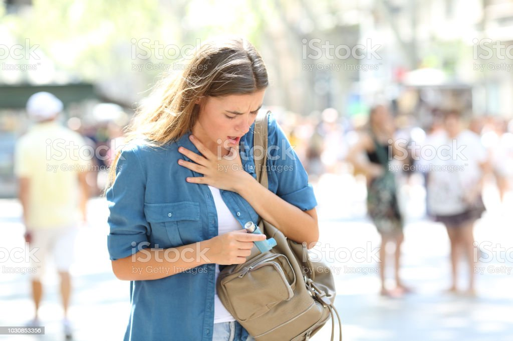 Asthmatic girl suffering an attack and searching inhaler stock photo