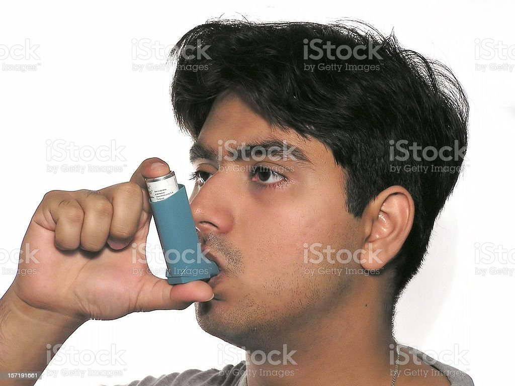 Asthmatic man using his inhaler stock photo
