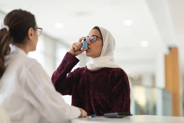 Asthmatische Frau verwendet Inhalator, während der Begegnung mit ihrem Arzt – Foto