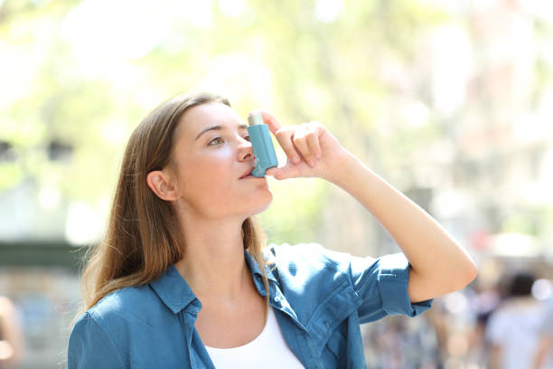 Asthmatic woman using inhaler standing in the street stock photo