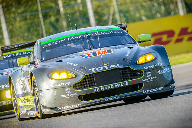 Aston Martin Racing Aston Martin Vantage V8 race cars Spa, Belgium - May 7, 2016: Aston Martin Racing Aston Martin Vantage V8 racing cars driving through Les Combes. The No. 98 car finished first in the LMGTE Am class. A second Aston Martin is following in the background. The car is driving around the Spa Francorchamps race track during the WEC 6 Hours of Spa-Francorchamps. The team participates in the 2016 FIA World Endurance Championship (WEC). spa belgium stock pictures, royalty-free photos & images