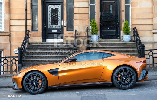 Glasgow, Scotland - Side view of a gold coloured Aston Martin Vantage (2018 onwards model) on a residential street.