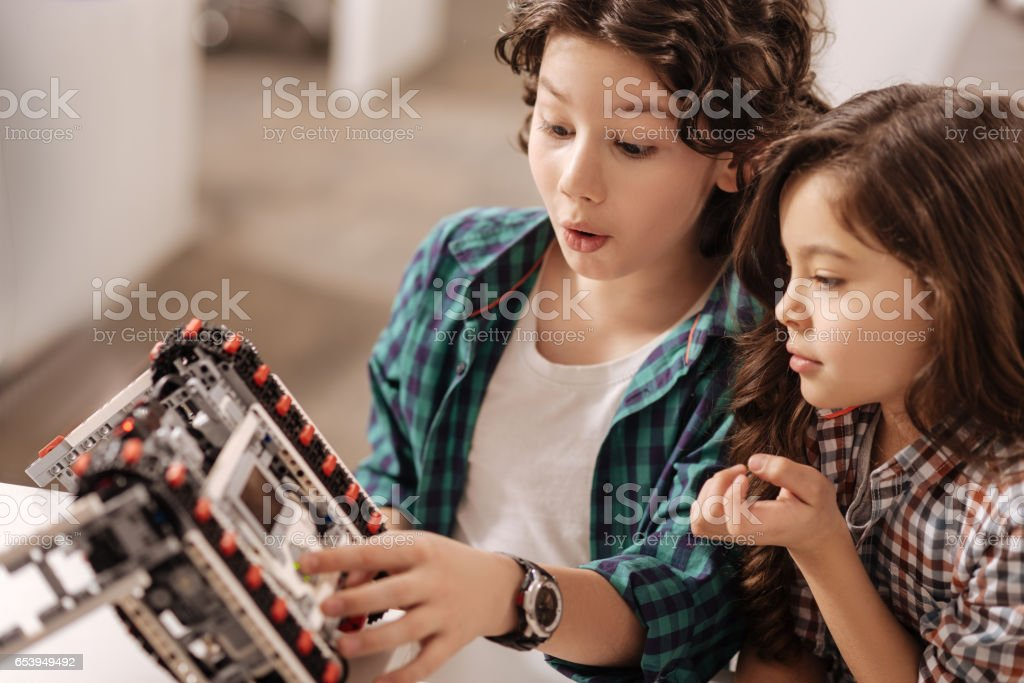 Astonished children programming robot in the science studio stock photo