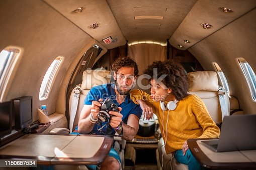 Amazed couple looking at photos from a dslr camera while flying on a private airplane.