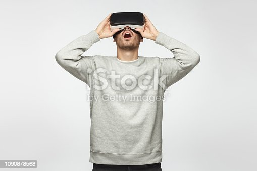 1090878574istockphoto Astonished man experiencing virtual reality while using VR headset for entertaining. People, technology and innovation concept. 1090878568