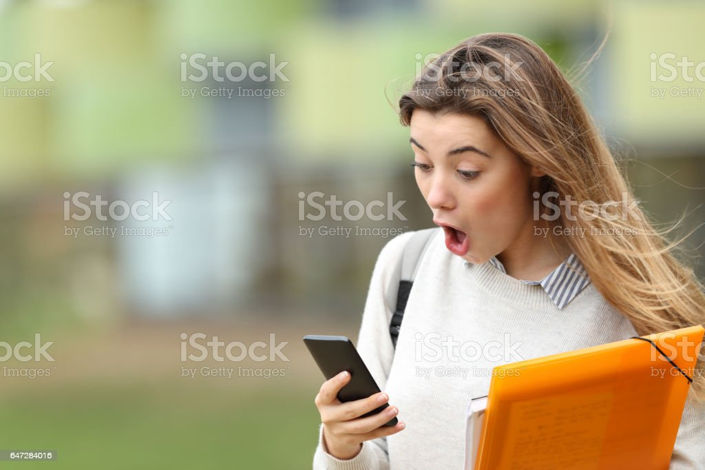 Astonished student receiving news on a smart phone - foto de stock