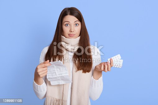 Astonished woman holding pills with instruction and looking at camera with puzzled facial expression, don't know how to take medicine, wearing white sweater and scarf, isolated over blue background.