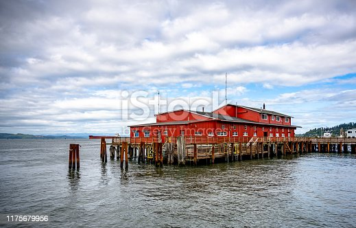 Red commercial wooden buildings of an old fishing and pilot pier with metal piles protruding from the water at the wide mouth of the Columbia River in Astoria city on the Pacific coast