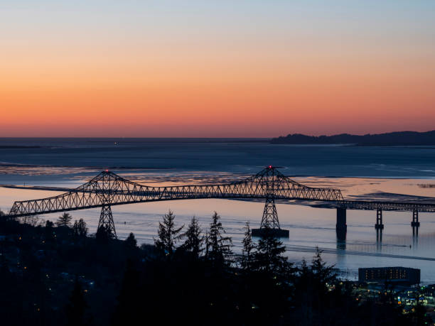 Astoria–Megler Bridge Columbia River at Astoria Oregon Evening Sunset An evening look at the bridge spanning the Columbia River from Oregon to Washington State. This is the Astoria–Megler Bridge. Crosses from Astoria Oregon to near Megler, Washington. Is unusually long at a little over 4 miles. oregon us state stock pictures, royalty-free photos & images