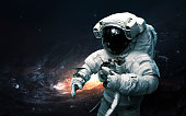 Astronaut against galaxy. Science fiction art. Elements of this image furnished by NASA