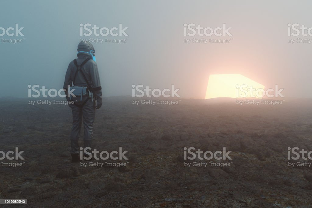 Astronaut and glowing alien cube stock photo