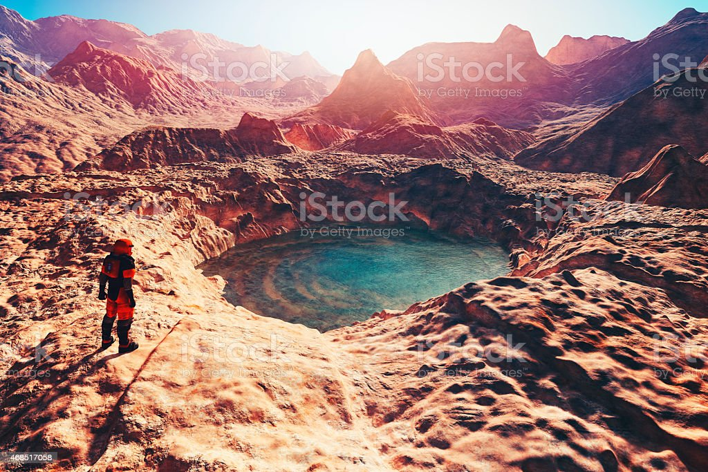 Astronaut discovering water on planet Mars stock photo