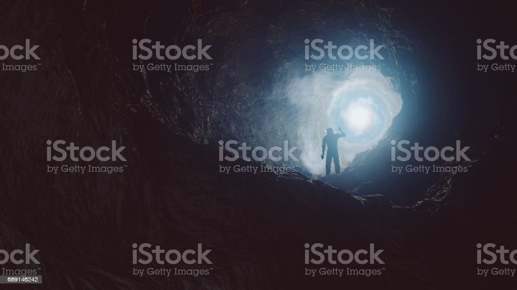 Astronaut entering cave on alien planet stock photo