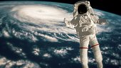 Astronaut falls to Earth in the open space. Spacewalk. Earth with a Hurricane. Elements of this image furnished by NASA. \