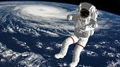 Astronaut falls to Earth in the open space. Spacewalk. Earth with a Hurricane. Elements of this image furnished by NASA