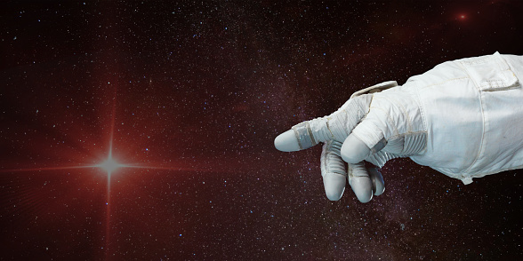 Astronaut hand pointing toward the star with background of deep space. Elements of this image furnished by NASA.
