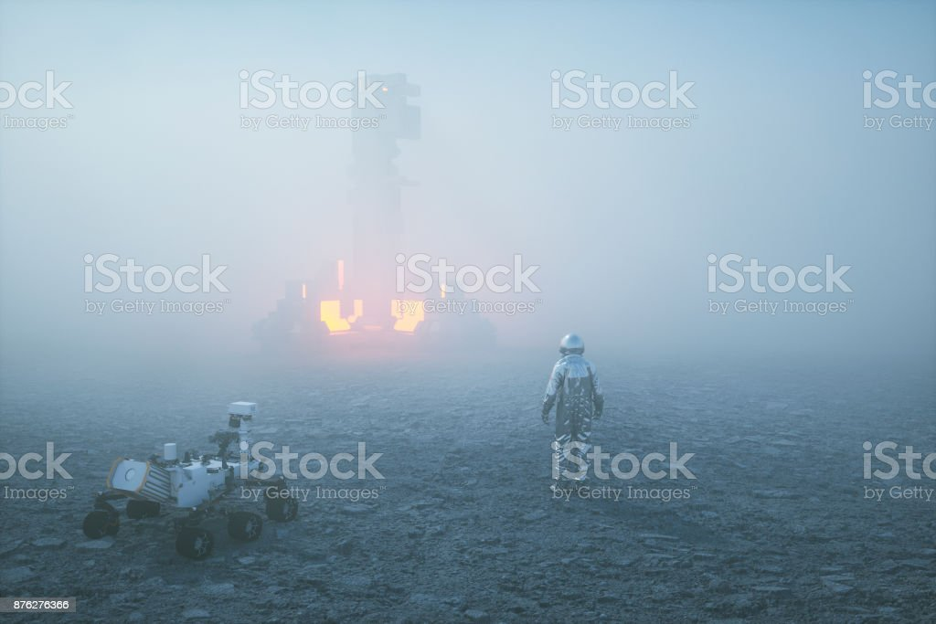 Astronaut in fog against alien object stock photo